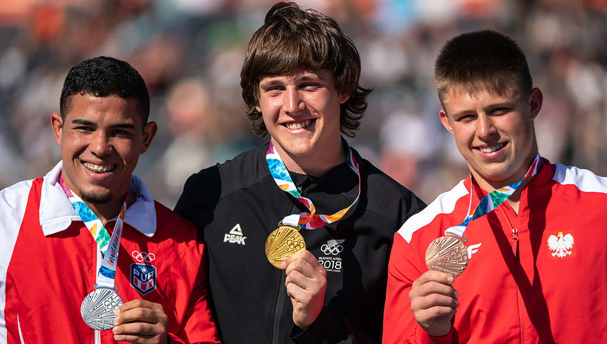 Men's discus gold medallist Connor Bell (NZL), pictured centre, managed to avoid a head-shave (Thomas Lovelock for OIS/IOC)