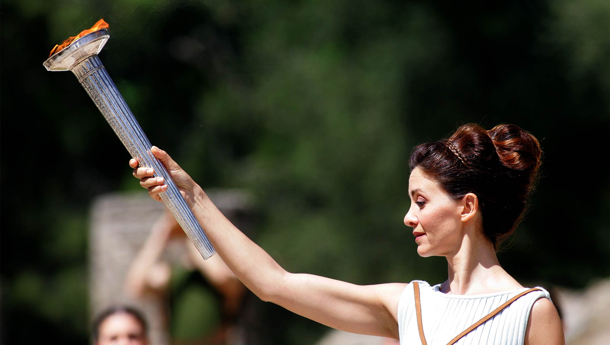 Woman dressed as a high priestess holding the torch