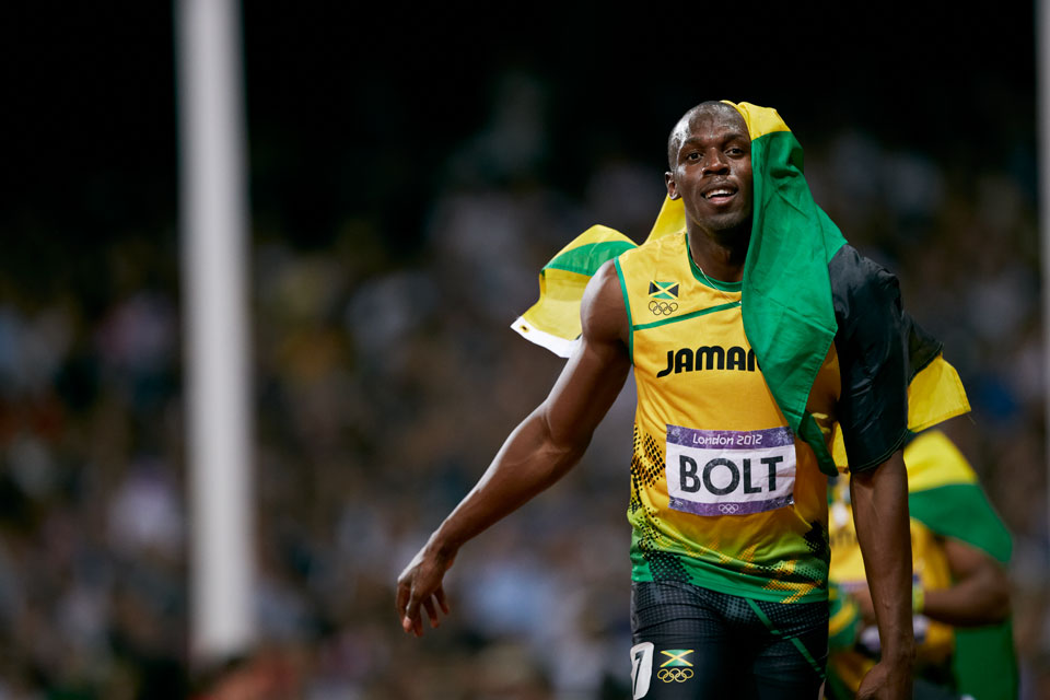 Usain Bolt smiles with a Jamaican flag draped over his head